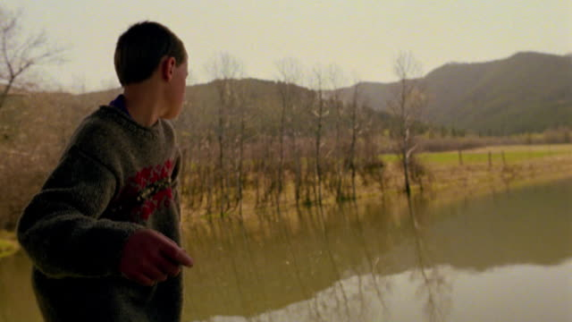 slow motion REAR VIEW MS point of view toward boy throwing/skipping stone into pond / mountains in background / Montana