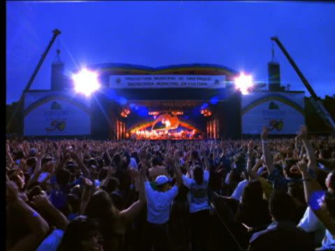 vídeos y material grabado en eventos de stock de slow motion rear view tracking shot large concert audience dancing + waving arms at outdoor evening concert - rock moderno