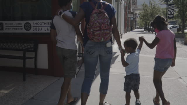 slow motion rear view tracking shot of family wearing protective masks walking on city sidewalk / provo, utah, united states - baby boys stock videos & royalty-free footage
