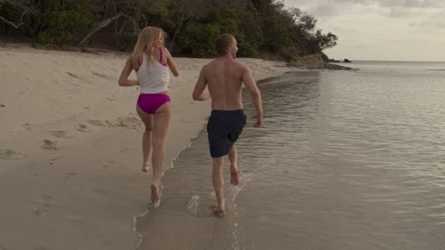slow motion rear view tracking shot of woman running on beach at sunset / anse la roche bay, carriacou, grenada - badbyxor bildbanksvideor och videomaterial från bakom kulisserna