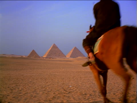 slow motion rear view two bedouins on horses running in desert toward great pyramids in background / giza, egypt - all horse riding stock videos & royalty-free footage