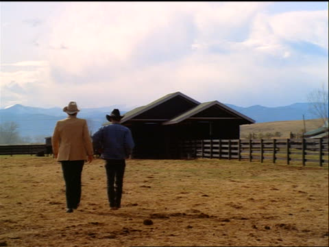 slow motion REAR VIEW two cowboys walking across corral toward cattle + buildings on ranch / Colorado