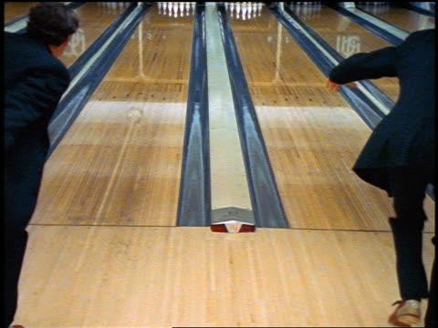 stockvideo's en b-roll-footage met slow motion rear view zoom in 2 men wearing suits bowling in bowling alley - compleet pak
