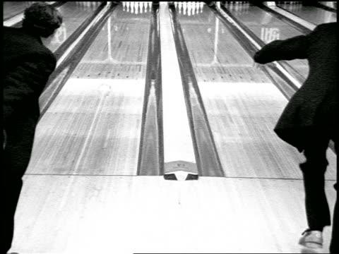 stockvideo's en b-roll-footage met b/w slow motion rear view zoom in two men wearing tuxedos bowling in bowling alley - compleet pak