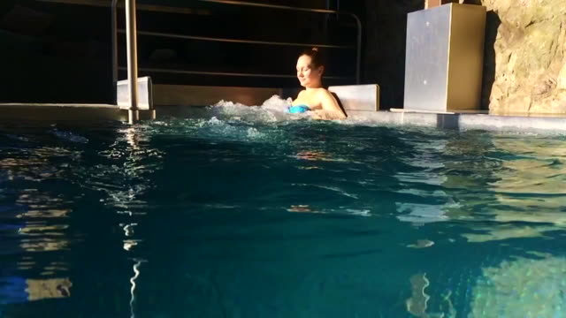 Slow motion recorded with smartphone of a girl enjoying hot tub in a warm swimming pool during winter time in the Catalan Pyrenees during a relaxed christmas vacations.