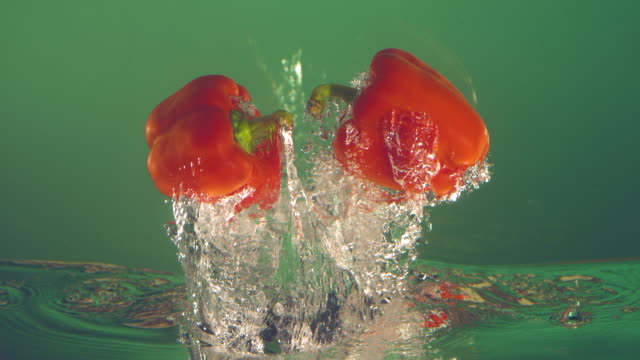 slow motion red bell pepper in water on green background - red bell pepper stock videos & royalty-free footage
