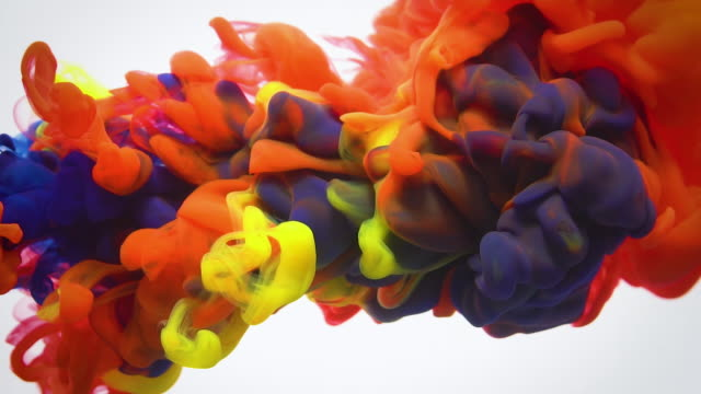 Slow motion red blue and yellow ink flow in water.