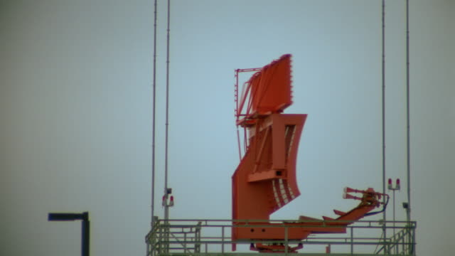 slow motion red radar antenna spinning on top of control tower at airport / airliner taking off in background