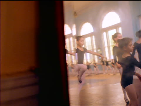 slow motion PAN reflection in mirror of young girls dancing in ballet class