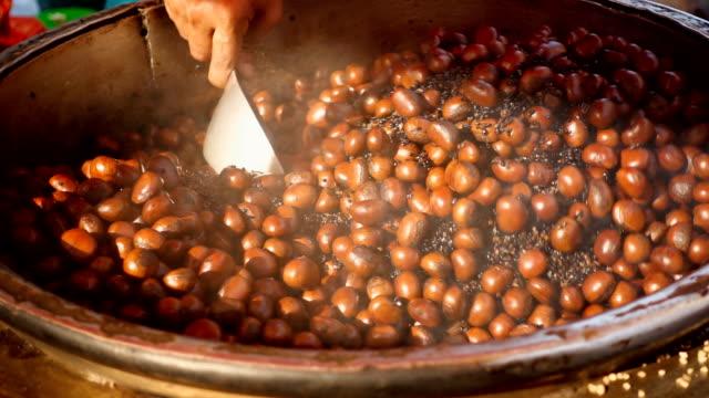 vídeos y material grabado en eventos de stock de cámara lenta: castañas asadas en un mercado de alimentos - marrón
