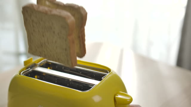 slow motion roasted toast bread popping up from toaster - toaster appliance stock videos & royalty-free footage