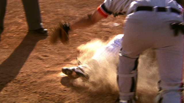 slow motion ms runner sliding into home + catcher attempting to tag runner out / umpire legs in background - baseballspieler stock-videos und b-roll-filmmaterial