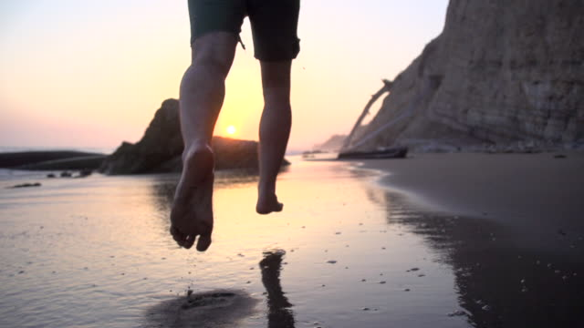 Slow motion running on the beach at sunset