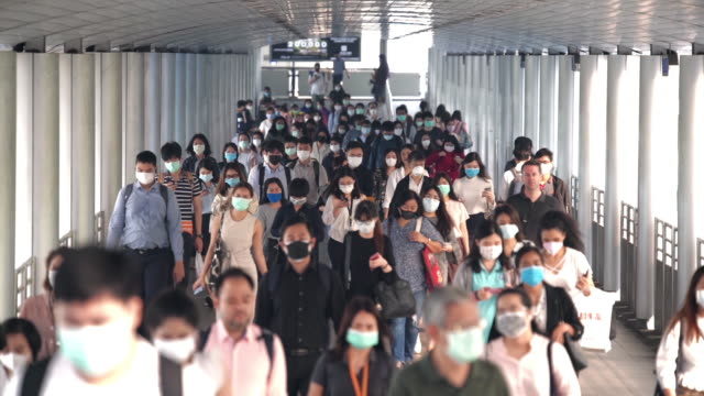 slow motion scene crowds of asian people wearing face protection in prevention for coronavirus or covid-19 and micro dust pm 2.5 in air while going to their workplace in bangkok at morning rush hour - crowd stock videos & royalty-free footage