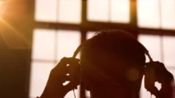 Slow motion Scene of a Young Attractive Man Wearing Headphones at a Window. Listening Music. Sunset in the City. Beautiful Orange Sun Flares.