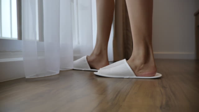 slow motion scene of asian woman wearing slippers after she wake up and walking to window in the morning - home sweet home stock videos & royalty-free footage