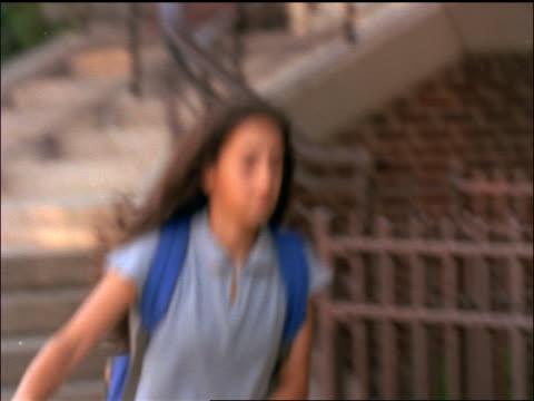 slow motion pan schoolgirl wearing backpack walking on sidewalk past school - solo adolescenti femmine video stock e b–roll