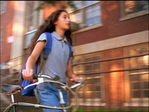 slow motion pan schoolgirl wearing backpack walking with bicycle on sidewalk - solo adolescenti femmine video stock e b–roll