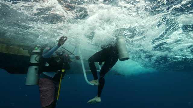 slow motion: scuba divers by boat in blue ocean - belize city, belize - aqualung diving equipment stock videos & royalty-free footage