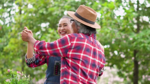slow motion: senior couple dancing in the garden with happiness. - mature couple stock videos & royalty-free footage