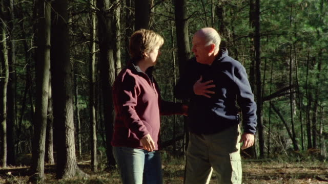vídeos de stock, filmes e b-roll de slow motion senior couple walking together in the woods / man clutching his chest and falling over / woman trying to revive him / taking out cell phone and dialing 911 - heart attack
