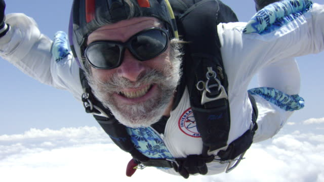 vidéos et rushes de slow motion - senior skydiver exhilarated in free fall - parachute