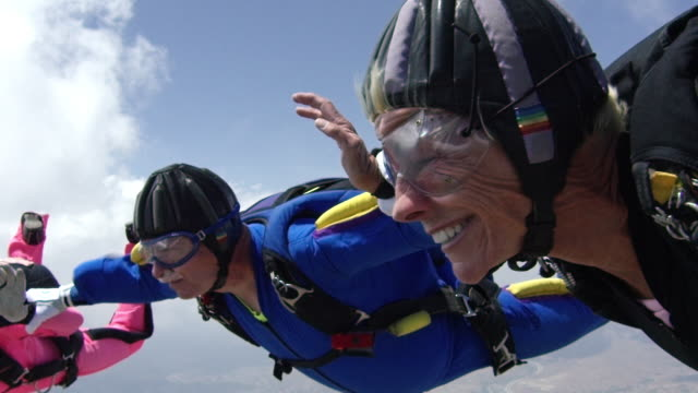 vídeos de stock e filmes b-roll de slow motion - senior skydivers smiling in free fall - atividade