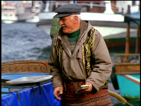 slow motion senior turkish man in hat takes food from unseen person on boat + gives it to man on dock - einzelner senior stock-videos und b-roll-filmmaterial