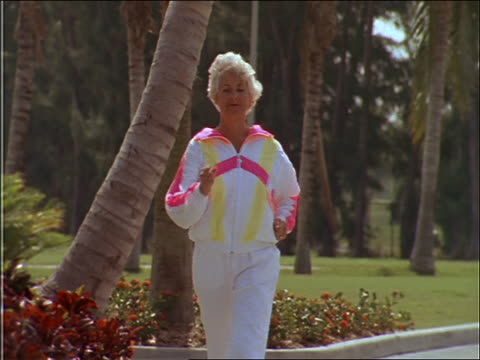 slow motion senior woman power walking toward camera - racewalking stock videos and b-roll footage