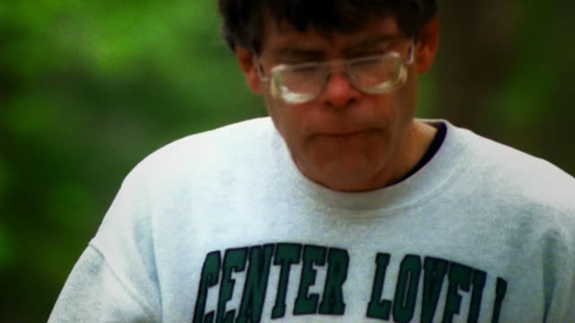 Slow motion sequence of Stephen King walking down a country path in Bangor Maine with his dog
