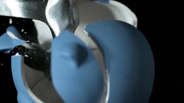vidéos et rushes de slow motion sequence showing a hammer smashing a blue piggy bank into pieces. - tirelire