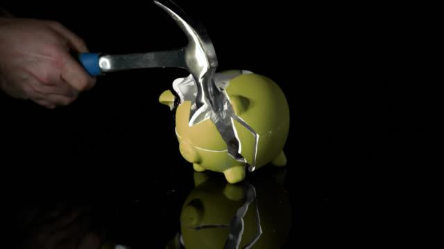 vidéos et rushes de slow motion sequence showing a hammer smashing a yellow piggy bank into pieces. - tirelire