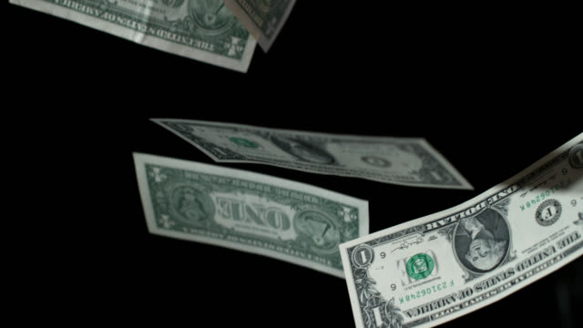 Slow motion sequence showing one dollar bills falling to the floor.