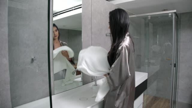 stockvideo's en b-roll-footage met 4k slow motion sexy meisje met behulp van een handdoek om het haar te vegen na het wassen van het haar - in een handdoek gewikkeld