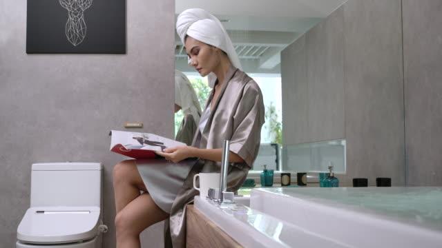 4k slow motion sexy woman in shape wear silk pajamas sitting reading near the bathtub - bath stock videos & royalty-free footage