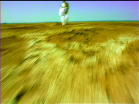 vídeos de stock, filmes e b-roll de slow motion shaky car point of view close up towards senior man in toga standing in desert holding fishing rod / panama - só um homem idoso