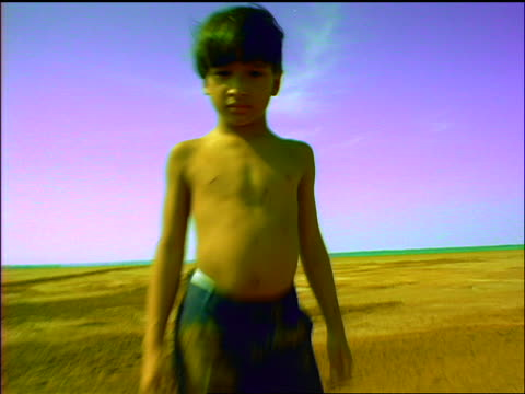 slow motion SHAKY car point of view towards + away from shirtless boy standing in desert looking at camera / Panama