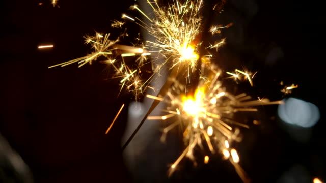 4kスローモーション 彼女は暗闇の中で花火を打っています。スパークラー付きの休日 - 玩具花火点の映像素材/bロール
