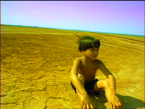 vídeos de stock, filmes e b-roll de slow motion shirtless boy sitting in desert with wind in hair / turns head + looks away / panama - dry