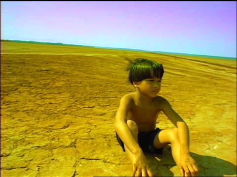 vídeos de stock, filmes e b-roll de slow motion shirtless boy sitting in desert with wind in hair / turns head + looks away / panama - clima árido