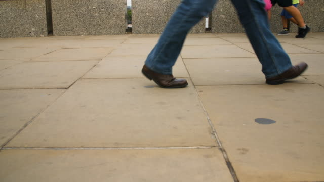 Slow motion shoot of pedestrians feet as they walk over London Bridge