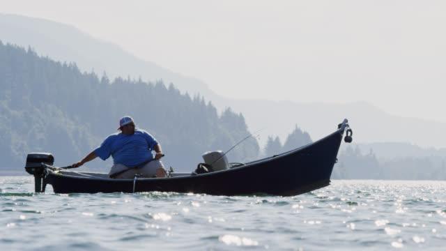 スローモーションは晴れた日にワシントンのコロンビア川で彼のボートを操縦する40代のヒスパニックの男を撃った - アメリカ太平洋岸北西部点の映像素材/bロール