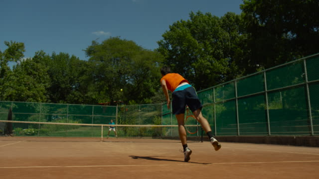 slow motion shot behind man serving tennis ball on clay court - backhand bildbanksvideor och videomaterial från bakom kulisserna