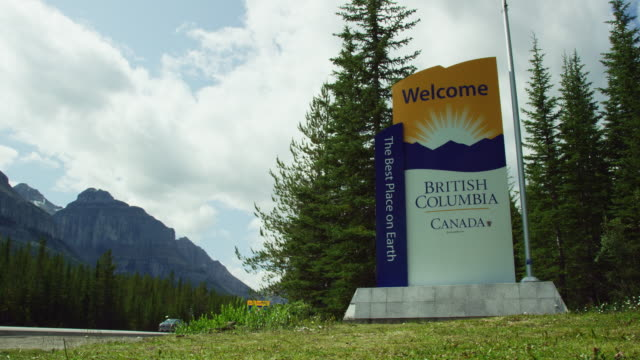"slow motion shot cars and vehicles passing a ""welcome--british columbia, canada, the best place on earth"" sign by the side of the road surrounded by the canadian rockies and forest on a partly cloudy day - place sign stock videos & royalty-free footage"