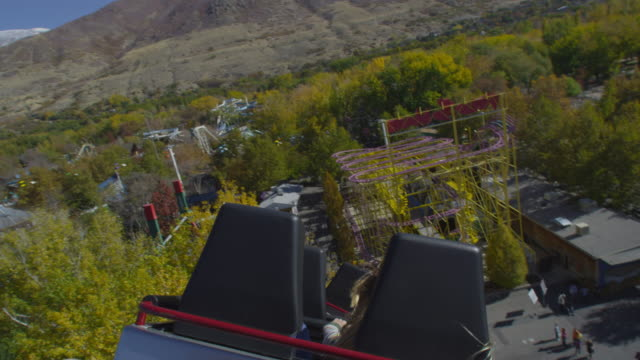 slow motion shot from the back of a rollercoaster riding the twists of the track. - roller coaster stock videos and b-roll footage