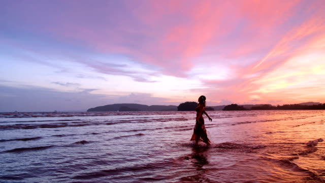 4K Slow motion shot : Middle age woman walking alone on the beach with beautiful sunset.