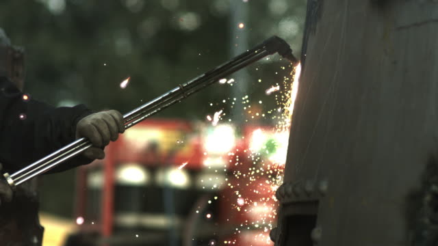 Slow motion shot of a acetylene torch cutting into metal.