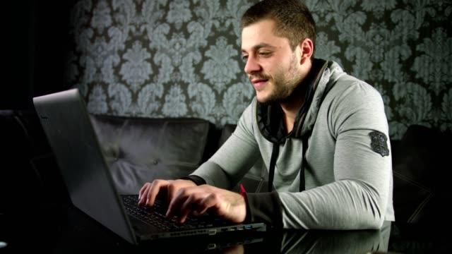 Slow-Motion-Aufnahme von ein schöner junger Mann auf der Couch sitzen und arbeiten auf einem Laptop zu Hause