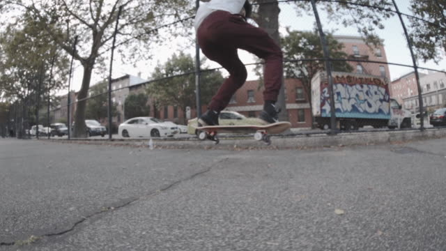 slow motion shot of a biracial man skateboarding through the streets of brooklyn - 柵点の映像素材/bロール