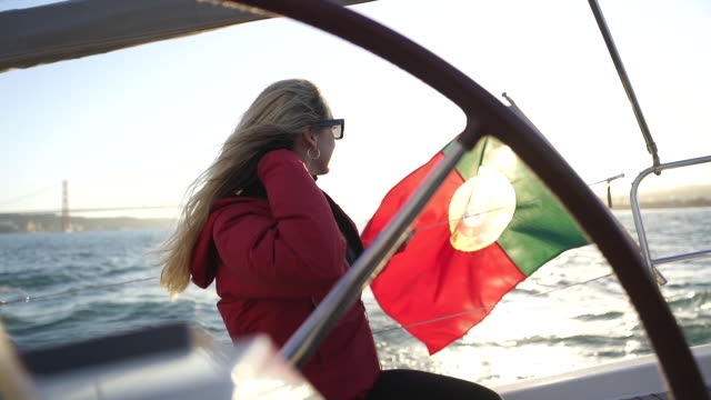vídeos de stock e filmes b-roll de slow motion shot of a blond woman whipping her hair on a boat - portugal